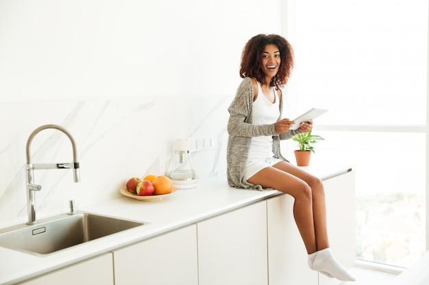 Z podnieceniem szczęśliwa afro amerykańska kobieta używa komputer osobisty pastylkę