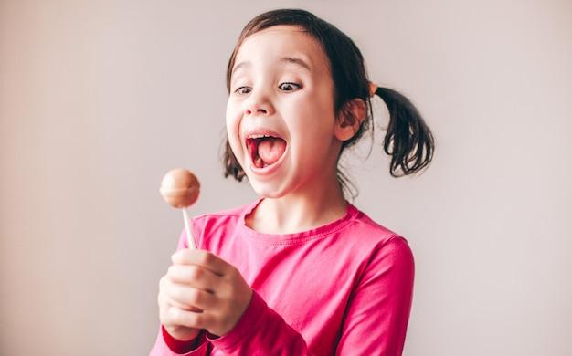 Z podnieceniem zadziwiające młode żeńskie dziecko odizolowywający nad ścianą. patrząc na lollipopa ze szczęścia i przyjemności.