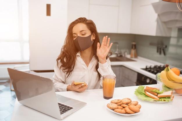 Z powodu pandemii koronawirusa, kobieta w izolacji w domu. pracuje w domu, nosi maskę i prowadzi wideokonferencję na swoim laptopie.