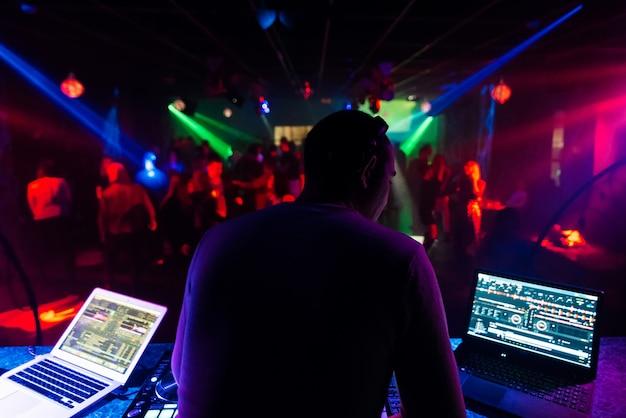 Z powrotem dj w słuchawkach miksuje muzykę na imprezie w klubie nocnym