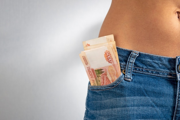 Z przedniej kieszeni dżinsów dziewczyny wystają kup 5 tysięcy rubli rosyjskich. kopia przestrzeń, poziome zdjęcie