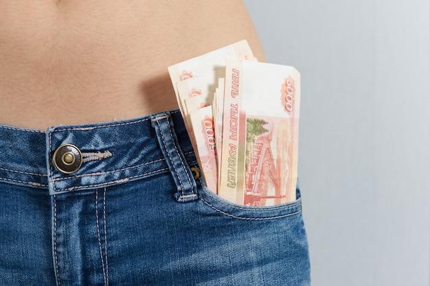 Z przedniej kieszeni dżinsów dziewczyny wystają kup 5 tysięcy rubli rosyjskich. zdjęcie poziome