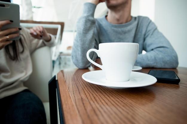 Z przodu biała filiżanka kawy. niewyraźna para na tle. mężczyzna i kobieta na romantyczną randkę w kawiarni. kawiarnia. kobieta trzymająca smartfona i wysyłająca sms-y, gdy mężczyzna czeka, aż skończy.