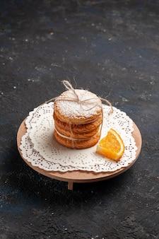Z przodu daleki widok ciasteczka kanapkowe z kremowym nadzieniem na ciemnej powierzchni ciasteczka ciasteczka