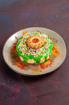 Z przodu daleki widok mały pyszny tort z zielonym kremem na ciemnej powierzchni ciasteczka biszkoptowe słodkie ciasto cukrowe
