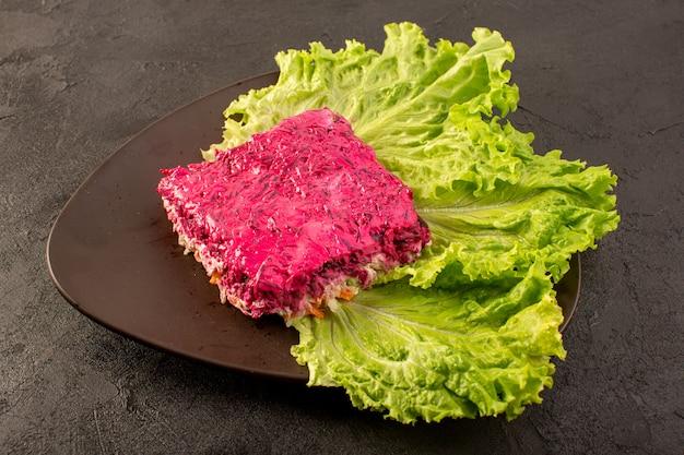 Z przodu zamknięty widok buraków sałatka plasterek majonezu wraz z zielonym wewnątrz brązowym talerzu