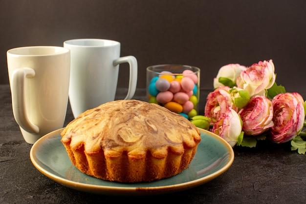 Z przodu zamknięty widok okrągły słodki tort pyszne pyszne ciasto wewnątrz niebieskiego talerza wraz z parą białych kubków, cukierków i kwiatów
