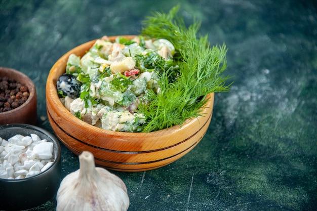 Z przodu zamknij widok sałatka jarzynowa z majonezem i zieleniną w małym garnku na ciemnym tle