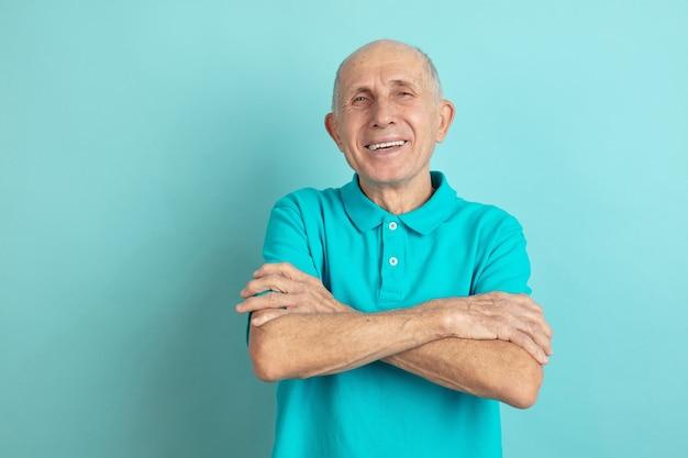 Z rękami skrzyżowanymi. portret rasy kaukaskiej starszego mężczyzny na białym tle na niebieskim tle studio. piękny męski model emocjonalny. pojęcie ludzkich emocji, wyrazu twarzy, sprzedaży, dobrego samopoczucia, reklamy. copyspace.