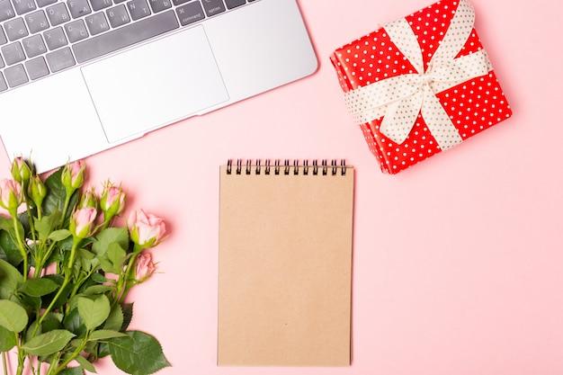 Z różowymi różami i pustym brązowym rzemieślniczym notatnikiem i pudełkiem gif. minimalistyczne mieszkanie leżał, różowe tło.
