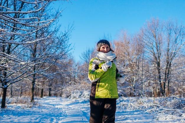 Z systemem kobieta lekkoatleta, sprint w lesie zimą. trening na zewnątrz w chłodne śnieżne dni.