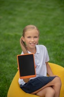 Z tabletem. śliczna jasnowłosa uczennica siedzi na krześle z torbą i pokazuje jej tablet