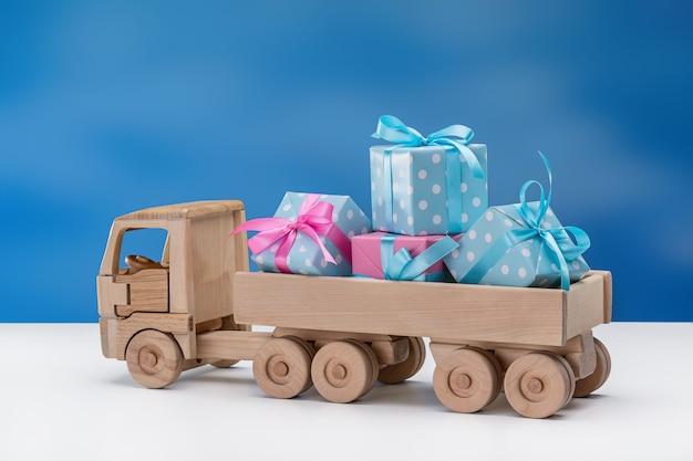 Z tyłu autka znajdują się świąteczne pudełka w kolorze niebieskim z białymi kropkami i różowym opakowaniem