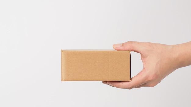 Z tyłu hand.hand trzyma brązowe pudełko na białym tle.