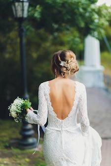 Z tyłu panny młodej w białej sukni trzyma bukiet róż