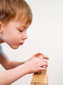 Z ukosa chłopiec bawi się drewnianą wieżą