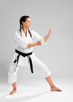 Z ukosa karate kobieta w tradycyjnym białym kimonie na białym tle