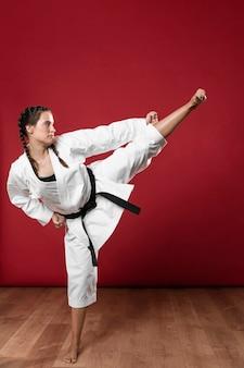 Z ukosa karate kobieta w tradycyjnym białym kimonie na czerwonym tle