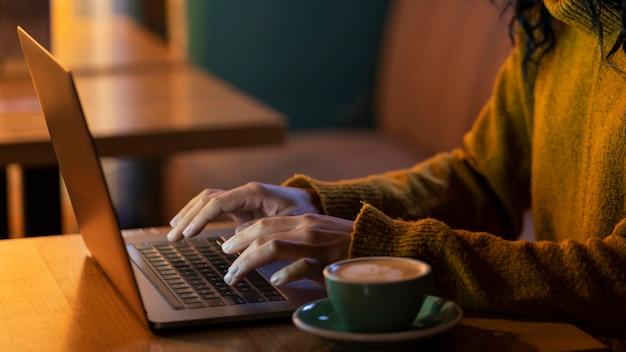 Z ukosa kobieta pracująca na swoim laptopie w kawiarni