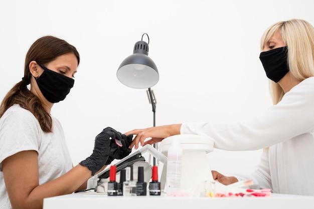 Z ukosa kobieta pracująca przy kliencie robi sobie normalne paznokcie