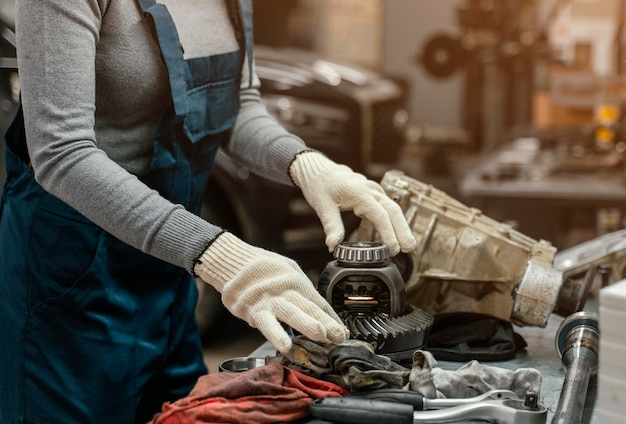 Z ukosa kobieta pracująca w serwisie samochodowym