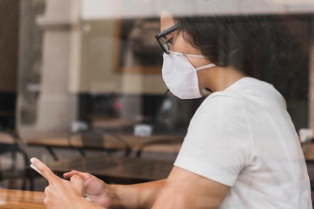 Z ukosa kobieta sprawdza jej telefon z medyczną maską