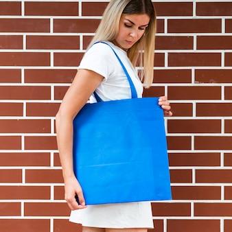 Z ukosa kobieta trzyma błękitną torbę