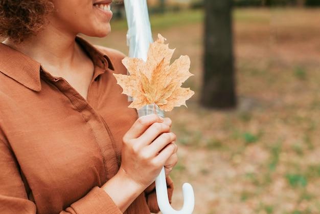 Z ukosa kobieta trzyma liść z miejsca na kopię