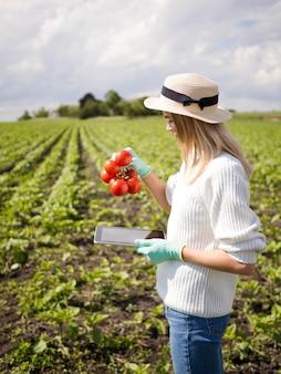 Z ukosa kobieta trzyma niektóre pomidory
