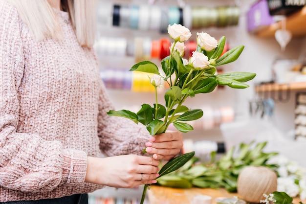 Z ukosa kobieta trzyma wiązkę kwiaty