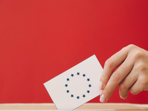 Z ukosa kobieta umieszcza europejską kartę do głosowania w pudełku