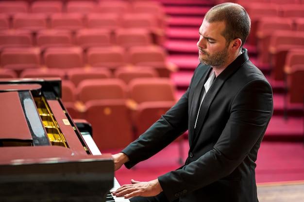 Z ukosa mężczyzna grający klasyczny recital fortepianowy