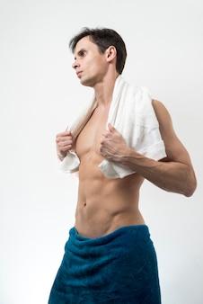 Z ukosa mężczyzna pozuje w kąpielowym ręczniku