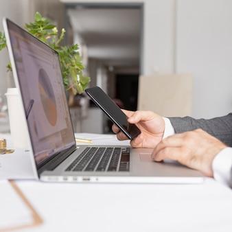 Z ukosa mężczyzna pracuje przy jego laptopem