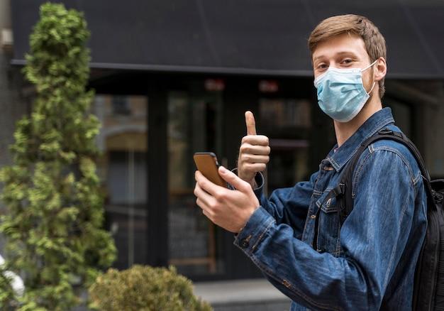 Z ukosa mężczyzna wychodzący na zewnątrz w masce medycznej z miejscem na kopię
