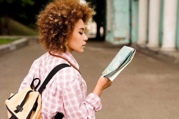 Z ukosa młoda kobieta sprawdza mapę