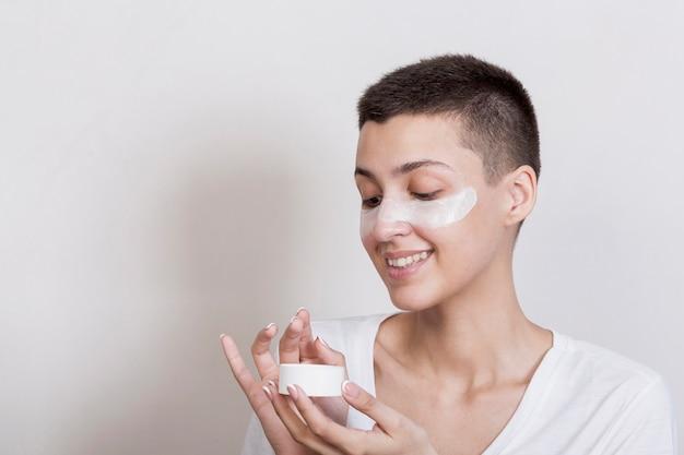 Z ukosa młoda kobieta stosuje śmietankę na twarzy