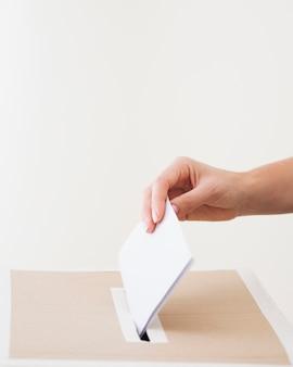Z ukosa osoba umieszczająca kartę do głosowania w polu wyborczym