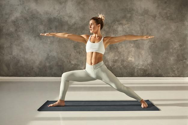 Z ukosa pełny obraz atrakcyjnej, muskularnej młodej kobiety ćwiczącej hatha jogę na siłowni, stojącej boso na macie w pozie virabhadrasana 2 lub warrior two, z skoncentrowanym wyrazem twarzy