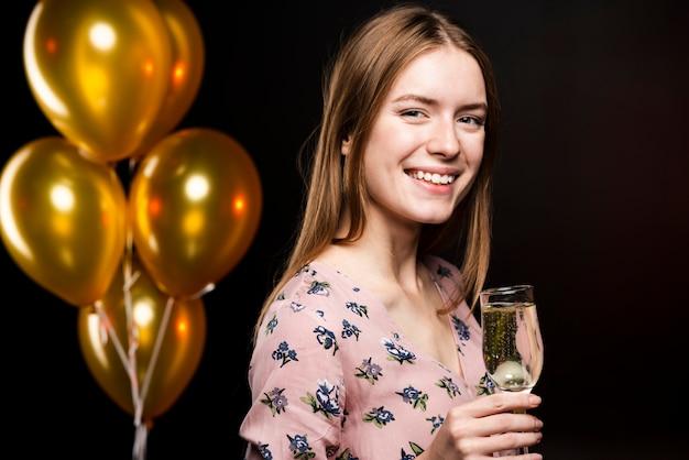 Z ukosa uśmiechnięta kobieta trzyma kieliszek szampana