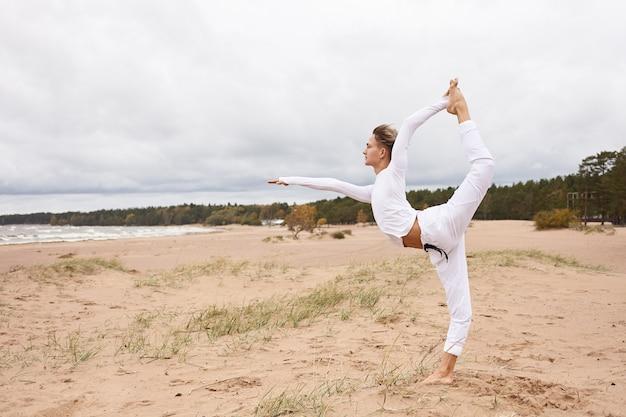 Z ukosa zdjęcie atrakcyjnego faceta stojącego boso z jedną stopą na piasku, wykonującego pozę natarajasana lub king dancer na bezludnej plaży. młody mężczyzna praktykujący jogę hatha na świeżym powietrzu nad morzem