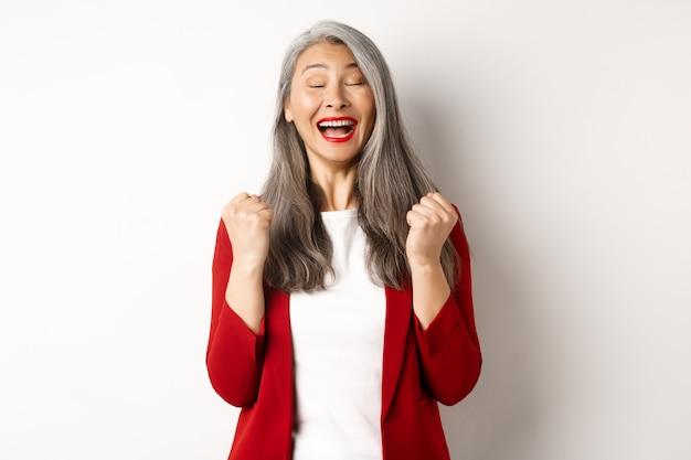 Z ulgą azjatycka starsza bizneswoman robi pompkę pięścią, mówiąc tak i uśmiechnięta zadowolona, triumfująca i wygrywająca, stojąca na białym tle.