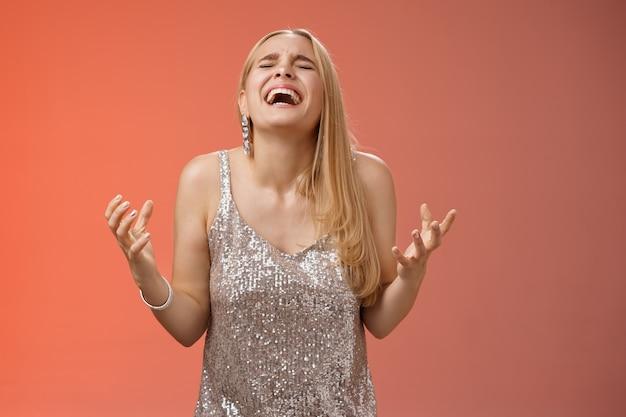Z ulgą szczęśliwa czarująca blond kobieta dziękuję bogu krzycząc tak świętuje radość wygrać stojąc czerwone tło zamknięte oczy śmiejąc się radość zaciśnięte pięści zwycięstwo triumf gest, marzenie się spełniło.
