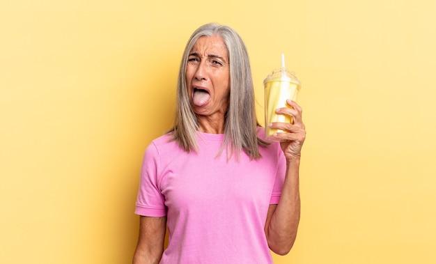 Z wesołym, beztroskim, buntowniczym nastawieniem, żartując i wystawiając język, bawiąc się i trzymając koktajl mleczny