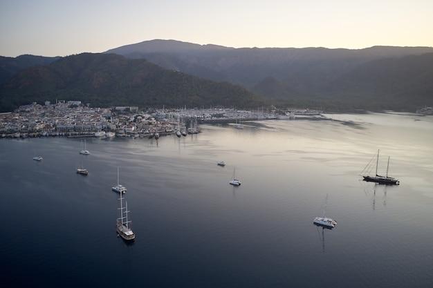Z widokiem na port w marmaris z górami w tle. statki na zatoce morskiej.