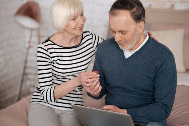 Z wielką miłością. uśmiechnięta starsza kobieta daje jakieś lekarstwo mężowi za pomocą laptopa siedząc na łóżku.