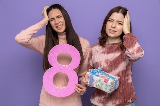 Z żalem kładąc ręce na głowie dwie dziewczyny w szczęśliwy dzień kobiet trzymające cyfrę osiem z prezentem