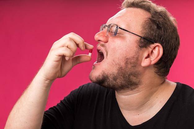 Z zamkniętymi oczami, chory mężczyzna w średnim wieku, próbujący pigułki