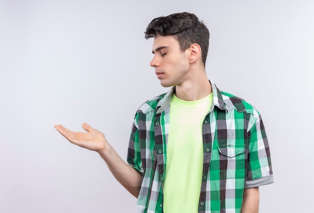 Z zamkniętymi oczami kaukaski młody chłopak ubrany w zieloną koszulę, wyciągając rękę na bok na białym tle
