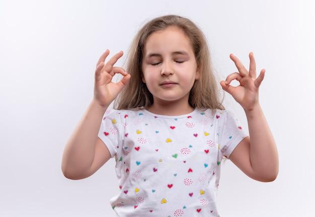 Z zamkniętymi oczami mała uczennica ubrana w białą koszulkę pokazująca gest okey na odosobnionej białej ścianie